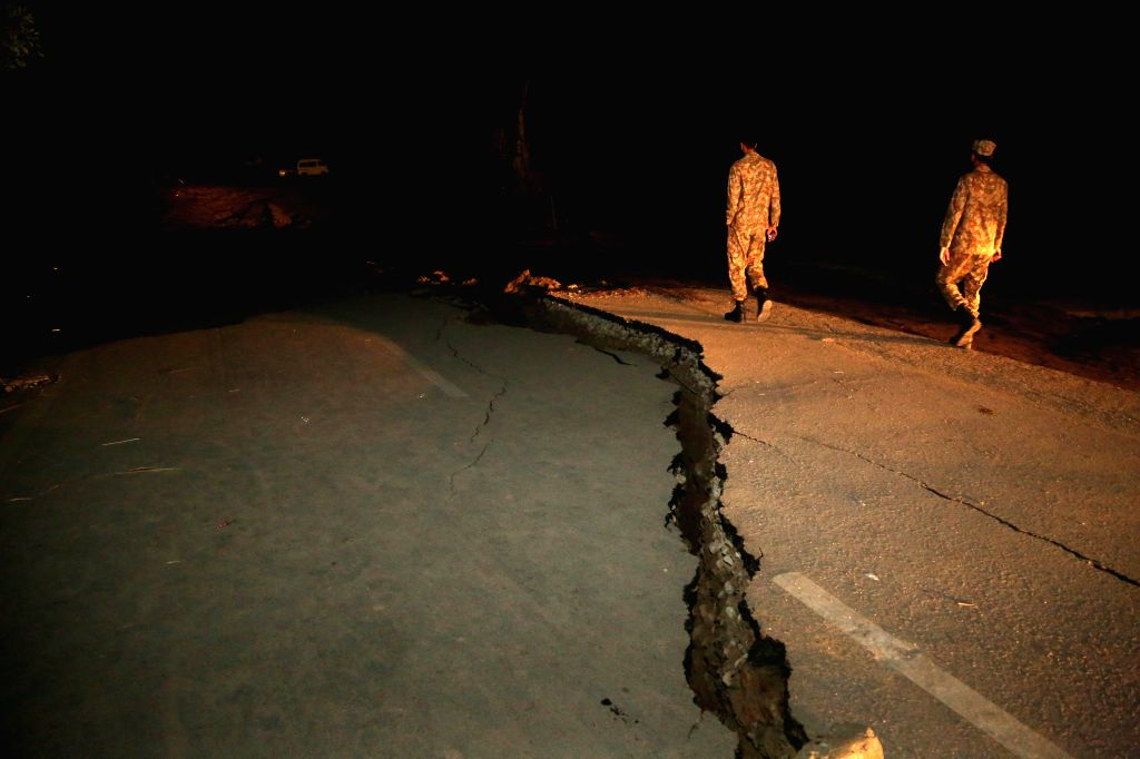 MIRPUR, Sept. 25, 2019 - Pakistani soldiers inspect a damaged road at the earthquake-hit area on the outskirts of Mirpur district of the Pakistan-controlled Kashmir on Sept. 25, 2019. Rescue efforts ...