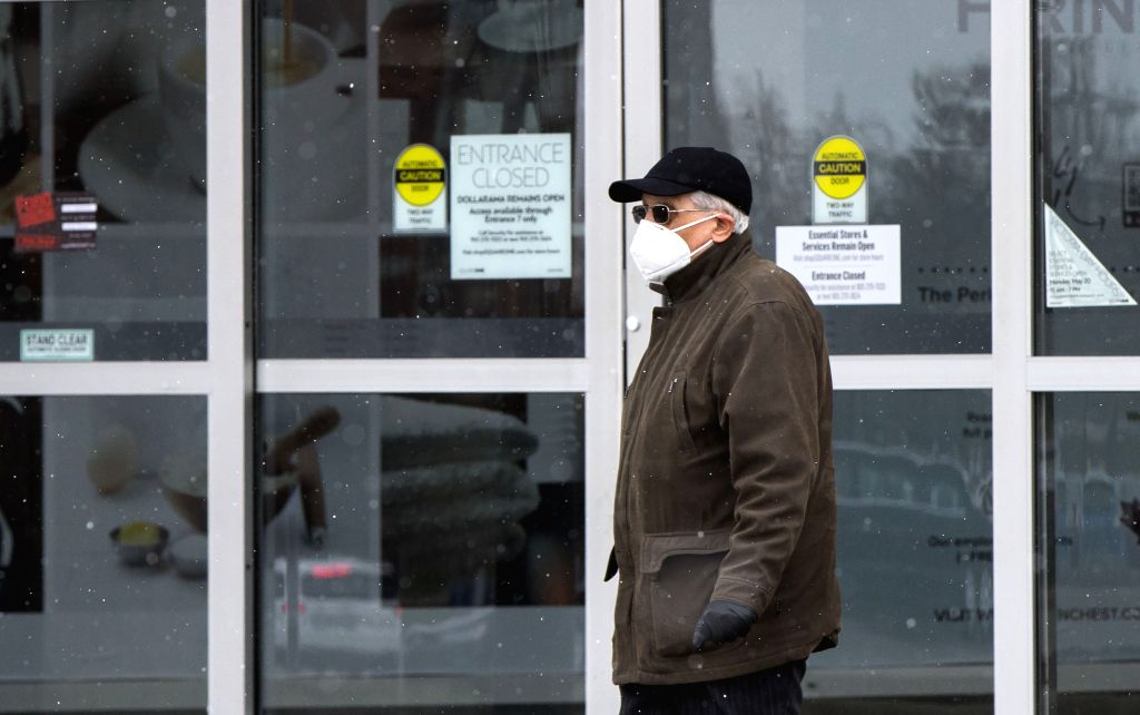 MISSISSAUGA (CANADA), May 8, 2020 A man wearing a face mask walks past the closed entrance of Square One Shopping Center in Mississauga, Ontario, Canada, on May 8, 2020. Canada's ...