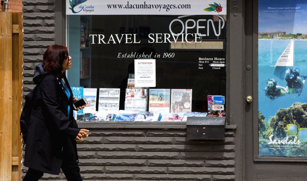 MISSISSAUGA (CANADA), May 8, 2020 A woman walks past a closed travel agency in Mississauga, Ontario, Canada, on May 8, 2020. Canada's unemployment rate soared to 13 percent as nearly 2 ...