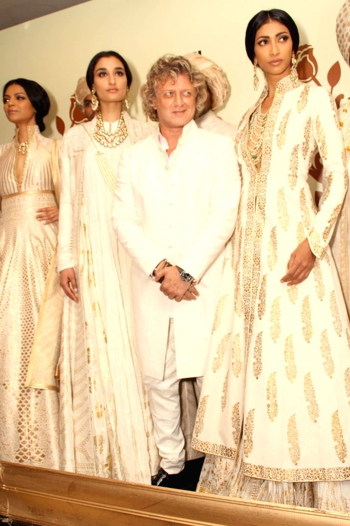 Models display designer Rohit Bal`s preview during India Couture Week 2014, in New Delhi on July 17, 2014.