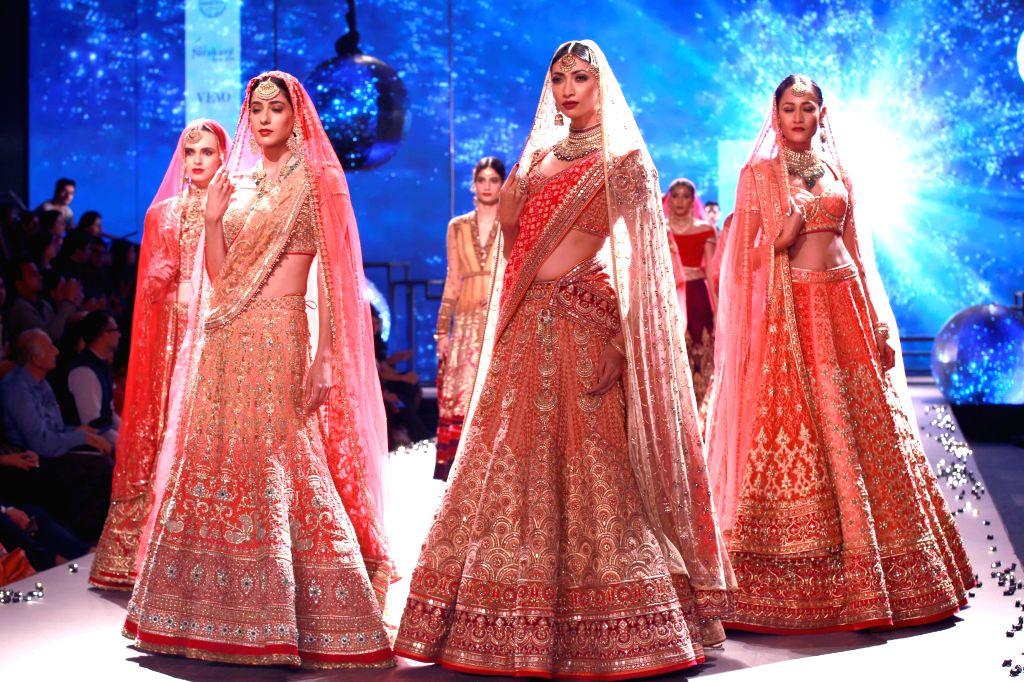 Models showcasing fashion designer Tarun Tahiliani's creation walk the ramp during BMW India Bridal Fashion Week in New  Delhi on Aug 8, 2015.