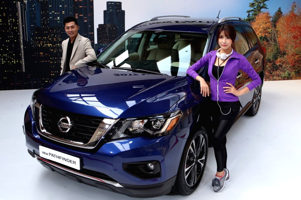 Models stand next to the new Pathfinder, a sports utility vehicle manufactured by Japan's Nissan Motor Co., during a publicity event in Seoul on Sept. 19, 2017.