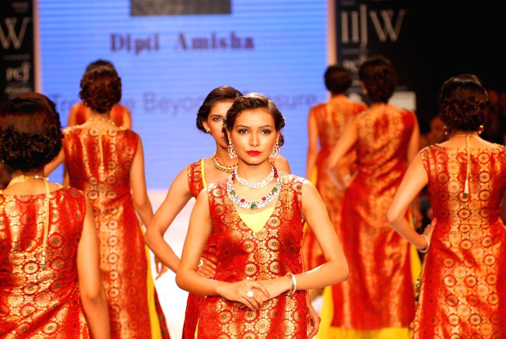 Models walk on the ramp displaying jewellery designed by Dipti Amisha during the India International Jewellery Week (IIJW) in Mumbai, on July 15, 2014.