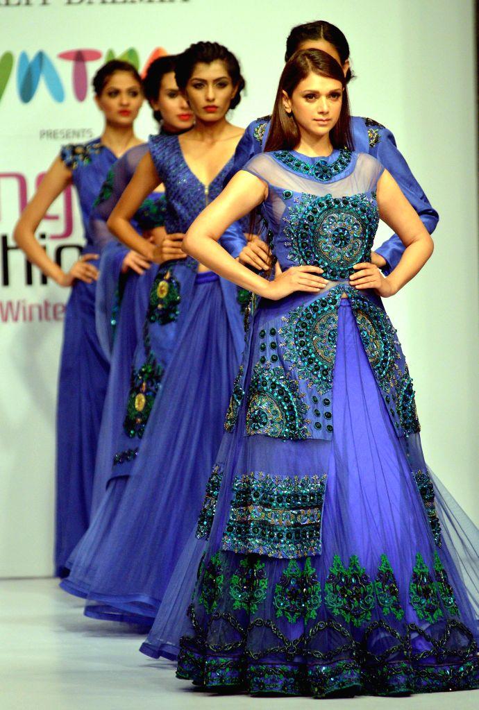 Models walk the ramp during Bangalore Fashion Week 2014, in Bangalore on Aug 8, 2014.