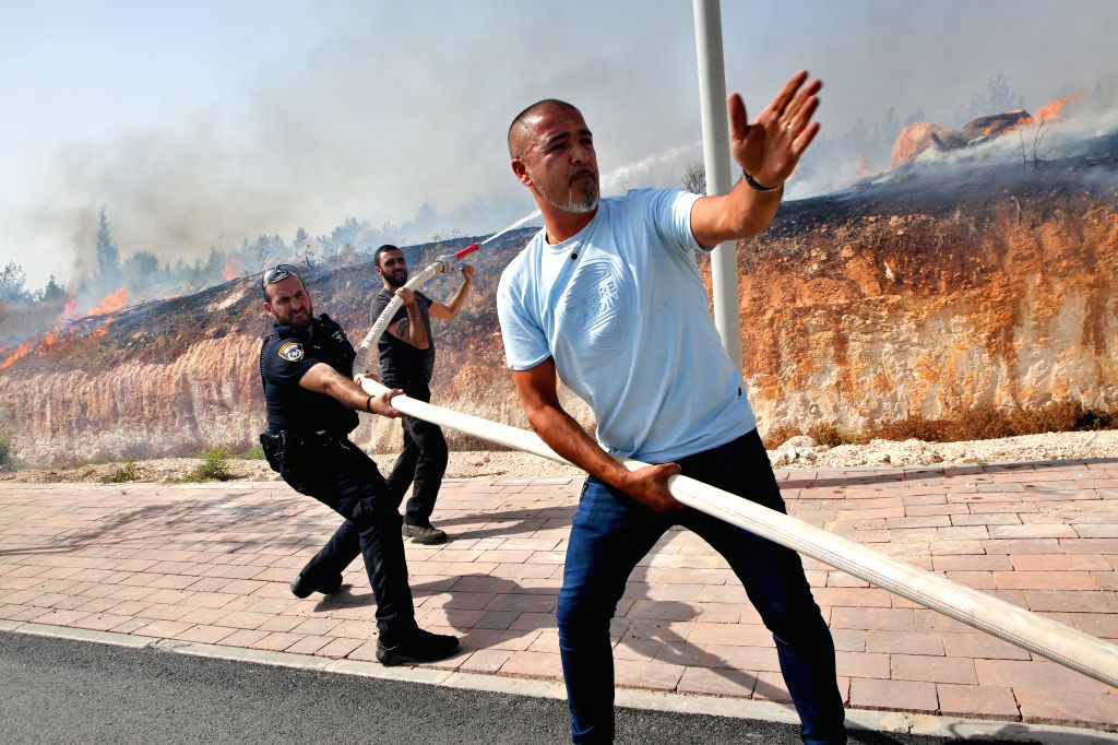 MODI'People try to put out a fire near Modi'in, Israel, on July 25, 2018. Israel is in the throes of a heat wave that has seen temperatures soaring to 40 degrees Celsius ...