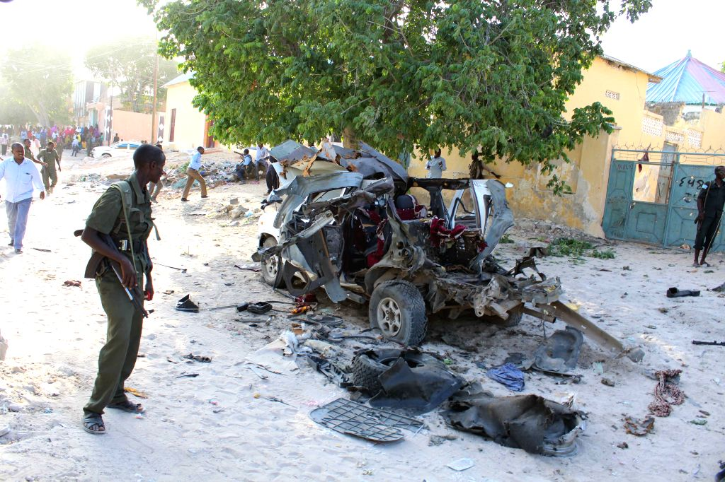 MOGADISHU, April 18, 2016 - A security officer looks at the wreckage of a car bomb explosion in Mogadishu, capital of Somalia, April 18, 2016. At least four people were killed in two separate ...