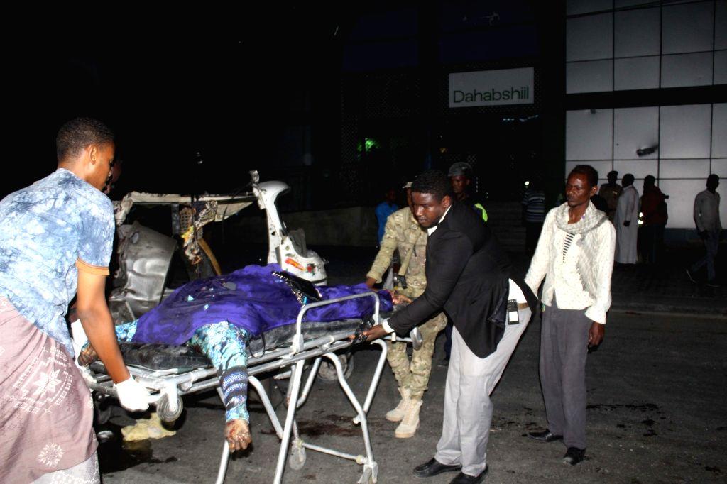 MOGADISHU, Aug. 4, 2017 - People transfer a body at a car bomb explosion site on Maka Almukarama road in Mogadishu, capital of Somalia, Aug. 4, 2017. At least three people were killed and scores ...