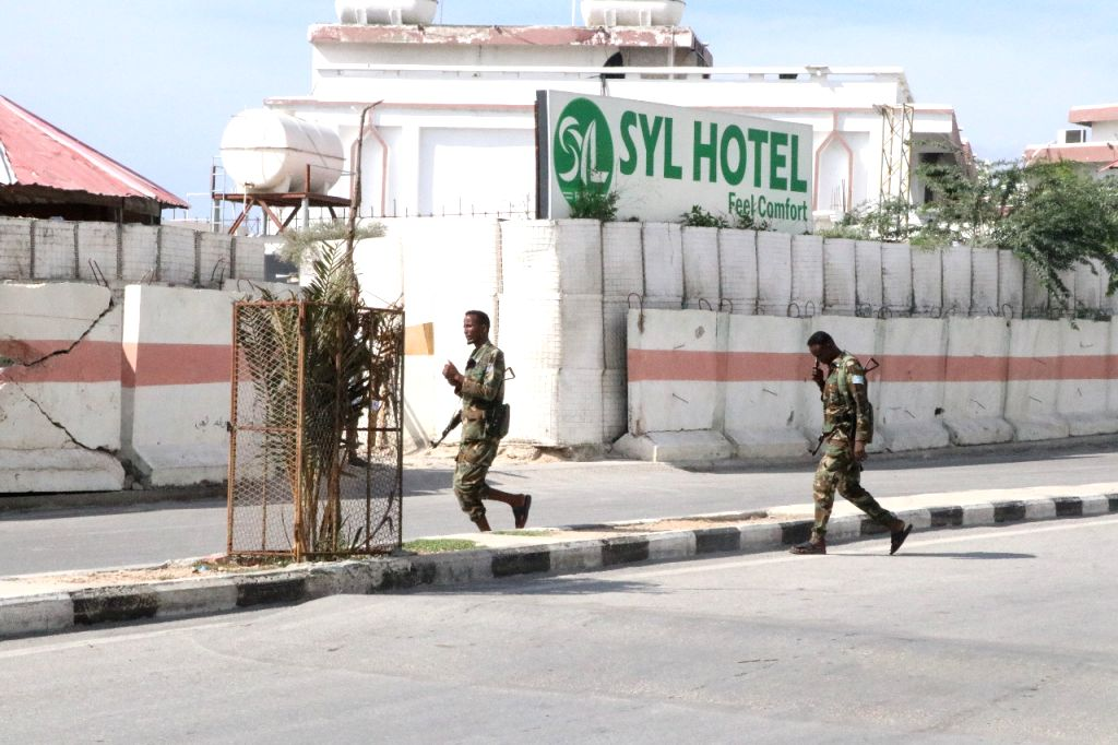 MOGADISHU, Dec. 12, 2019 - Security personnel patrol around the hotel attacked by militants in Mogadishu, capital of Somalia, Dec. 11, 2019. At least four people were killed and six others injured ...