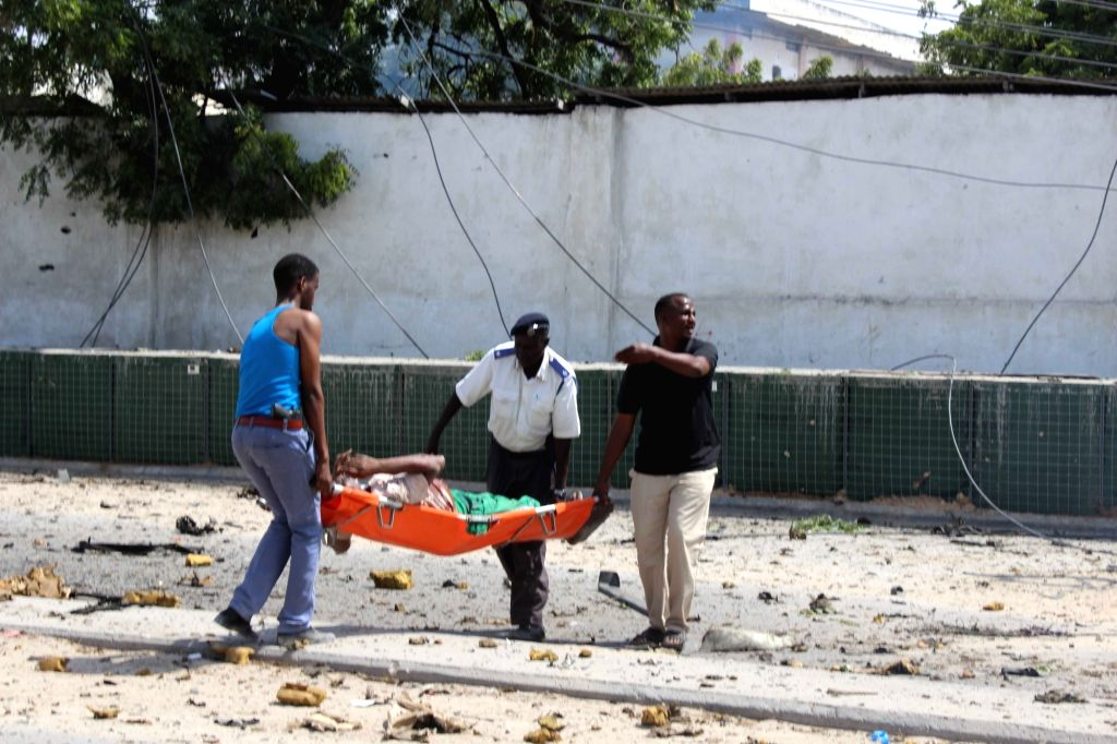 MOGADISHU, July 31, 2016 - People carry a wounded person after a car bomb explosion in Mogadishu, capital of Somalia, on July 31, 2016. At least five people were killed and several others were ...