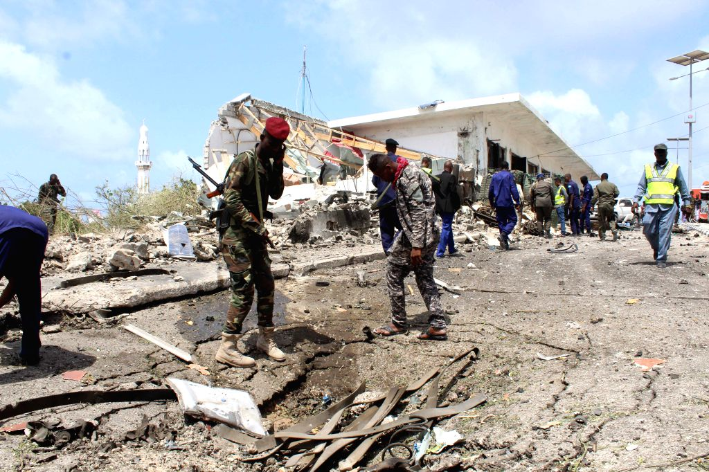 MOGADISHU, July 7, 2018 - Security force members inspect wreckages at the scene of an explosion in Mogadishu, Somalia, July 7, 2018. At least 12 people were killed and 17 others injured in twin ...