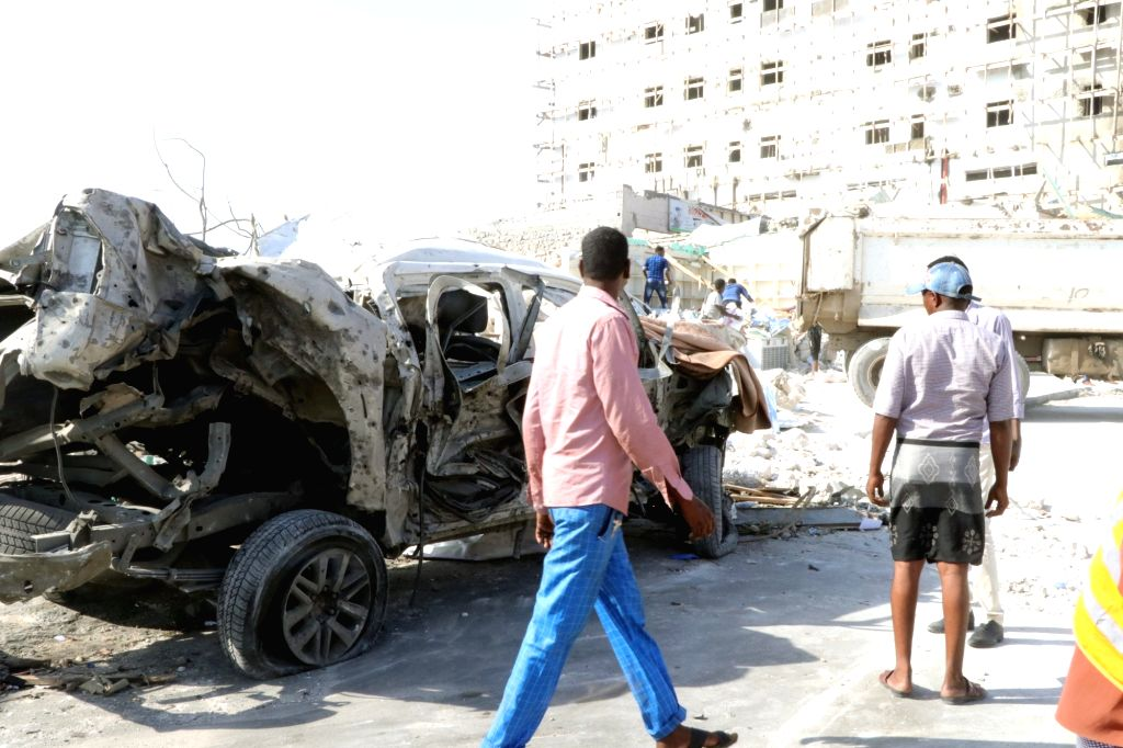 MOGADISHU, June 15, 2019 - Somalis walk past a destructed vehicle after a car bomb blast in Mogadishu, capital of Somalia, on June 15, 2019. At least 10 people were killed and 26 others injured in ...