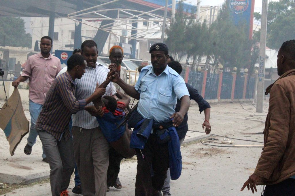 MOGADISHU, June 26, 2016 - People help an injured man out of the gunfire site by a notel Mogadishu, Somalia, June 25, 2016. Twin car bomb explosions rocked a hotel in the center of the Somali capital ...