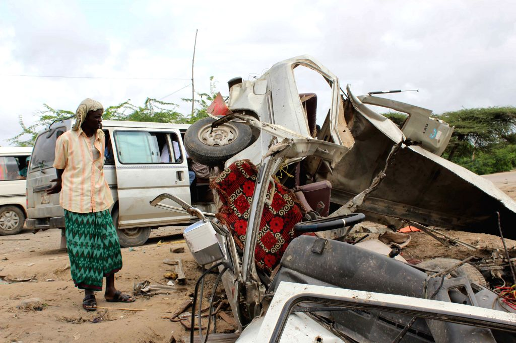 MOGADISHU, June 30, 2016 - A man looks at the remains of a minibus on the outskirt of Mogadishu, Somalia, June 30, 2016. At least 20 civilians traveling in a bus were killed in a roadside bomb attack ...