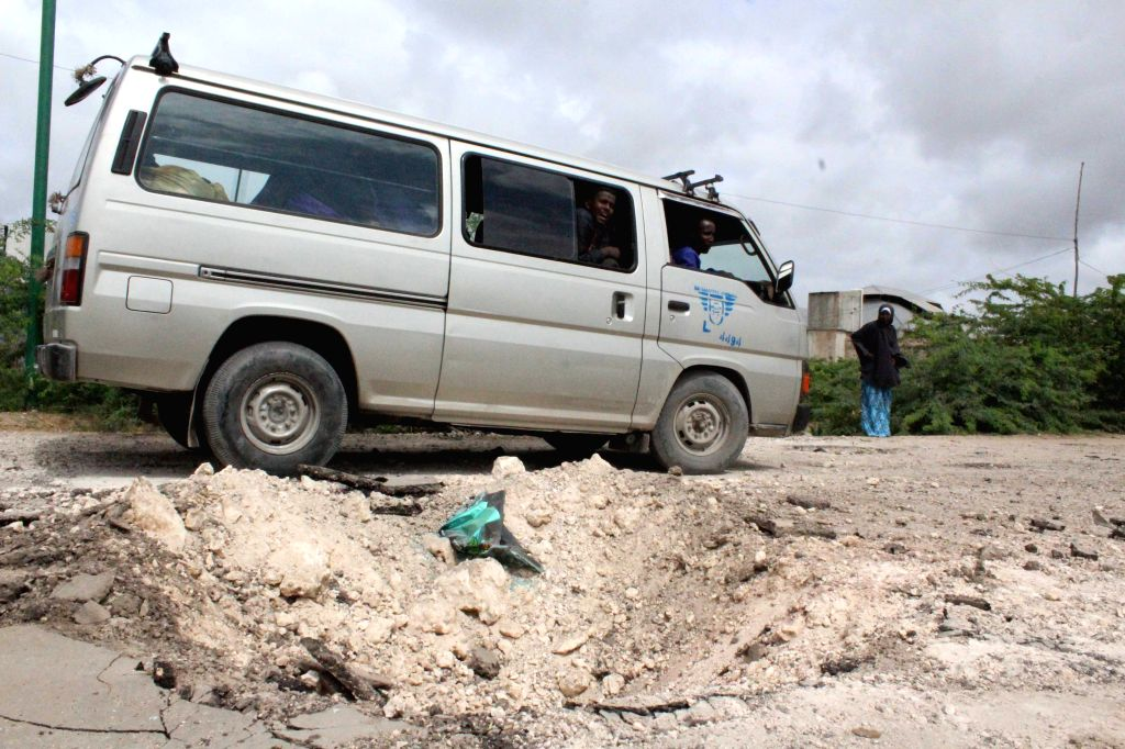 MOGADISHU, June 30, 2016 - A minibus drives past the site of a roadside bomb attack on the outskirt of Mogadishu, Somalia, June 30, 2016. At least 20 civilians traveling in a bus were killed in the ...
