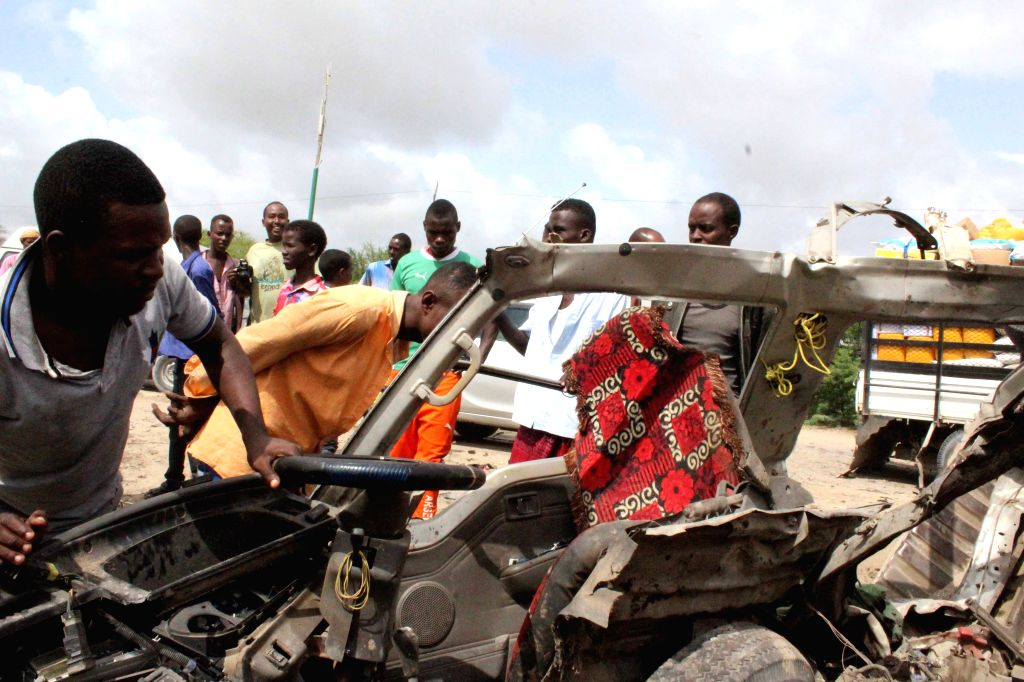 MOGADISHU, June 30, 2016 - Local people look at the remains of a minibus on the outskirt of Mogadishu, Somalia, June 30, 2016. At least 20 civilians traveling in a bus were killed in a roadside bomb ...