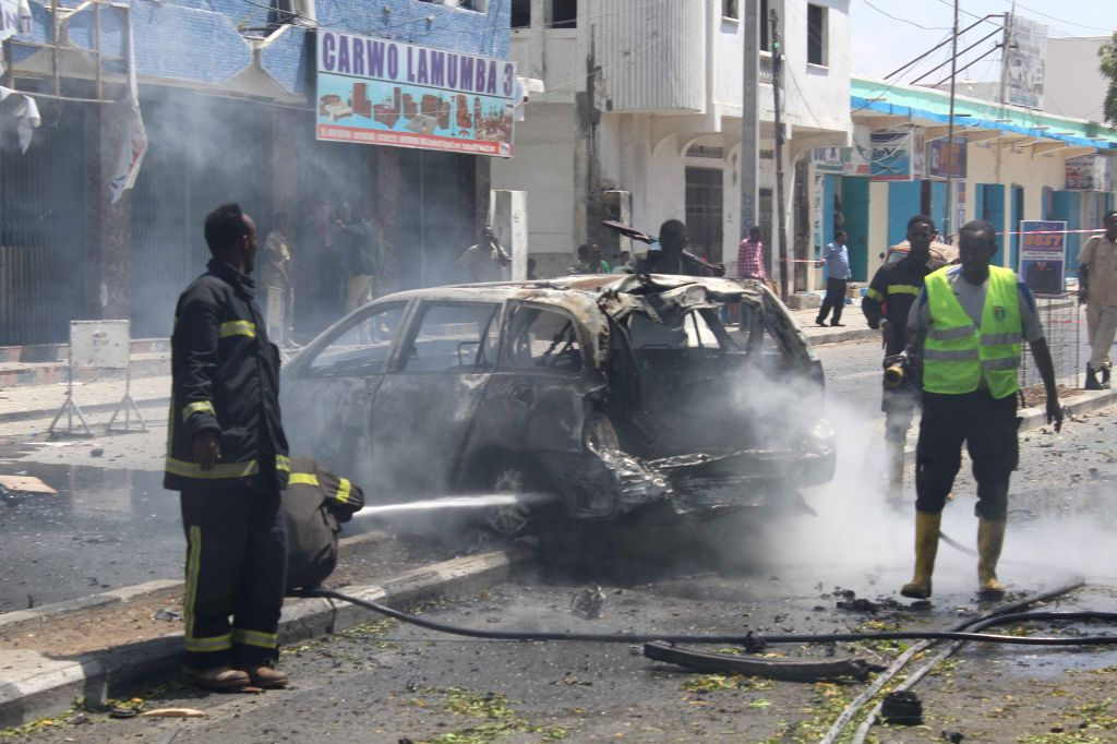 MOGADISHU, March 13, 2017 - Firefighters work at the site of a suicide attack in Mogadishu, Somalia, March 13, 2017. At least two people were killed in a car bomb blast in the Mogadishu on Monday, ...