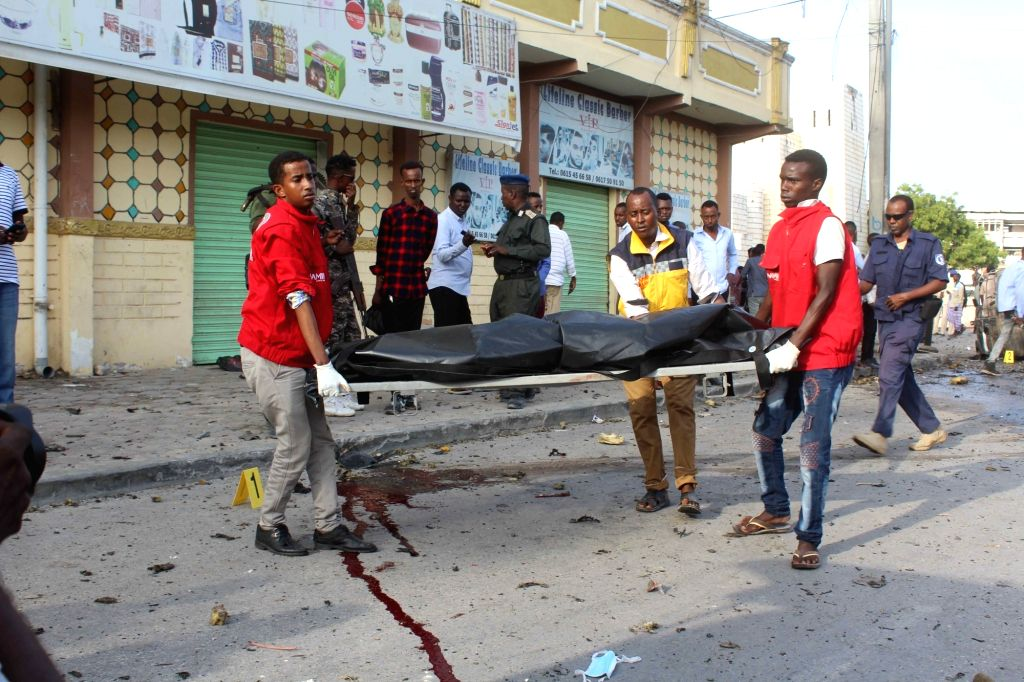MOGADISHU, March 25, 2018 - Rescuers carry the body of a victim at the explosion site in Mogadishu, capital of Somalia, March 25, 2018. At least five people were killed and several others injured ...
