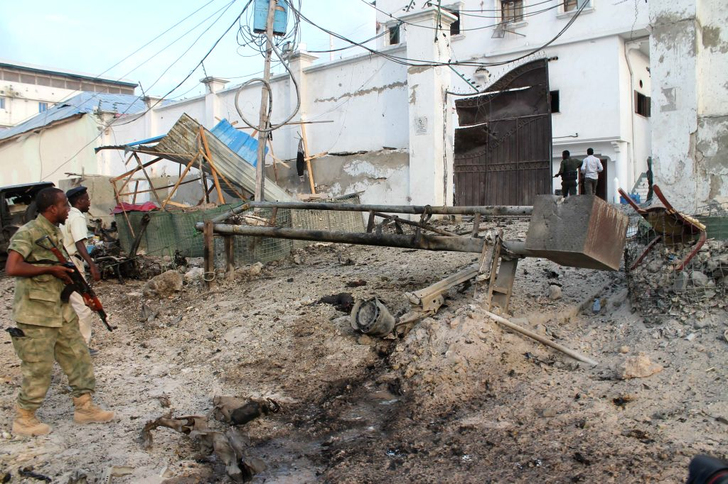 Police officers inspect the front gate of Maka Al-mukarama Hotel after an explosion in Mogadishu, capital of Somalia, on March 27, 2015. At least five people ...