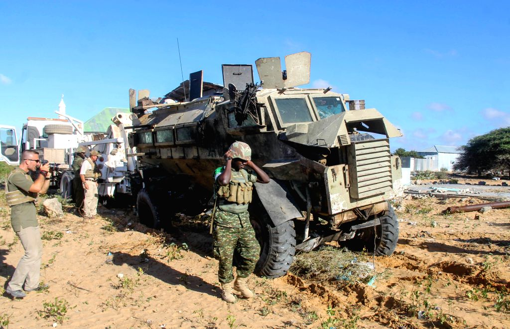 Investigators check the site of a suicide carbomb targeting a convoy of the African Union Mission in Somalia (AMISOM) on a road linking Mogadishu and Afgooye, a ..