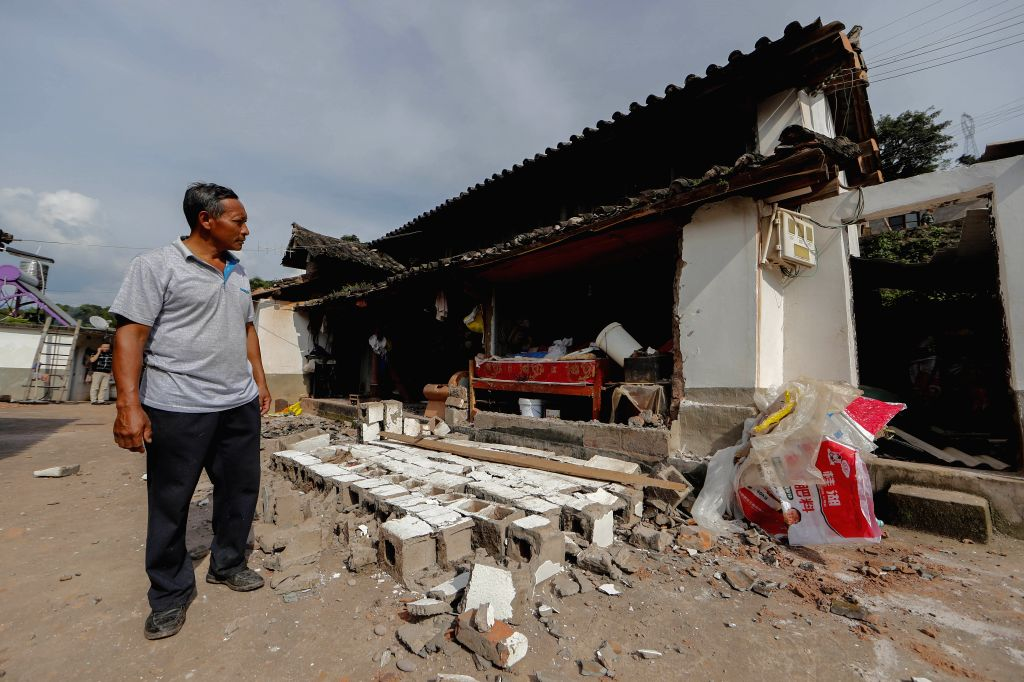 MOJIANG, Sept. 8, 2018 - A villager walks past his damaged house at Tongguan Township of Mojiang Hani Autonomous County, southwest China's Yunnan Province, Sept. 8, 2018. Fourteen people suffered ...