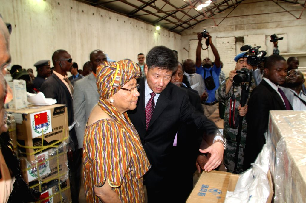 Chinese Ambassador to Liberia Zhang Yue (R front) introduces the emergency humanitarian supplies to Liberia's President Ellen Johnson-Sirleaf (L front) during a ...