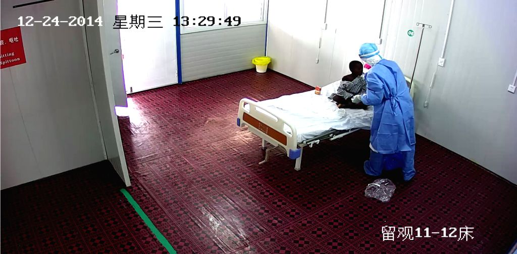 MONROVIA, Dec. 25 2014 The TV grab taken on Dec. 24 2014 shows a Chinese medical worker feeds water to a 7-year old boy who was confirmed Ebola patient, at the Chinese medical center in ..