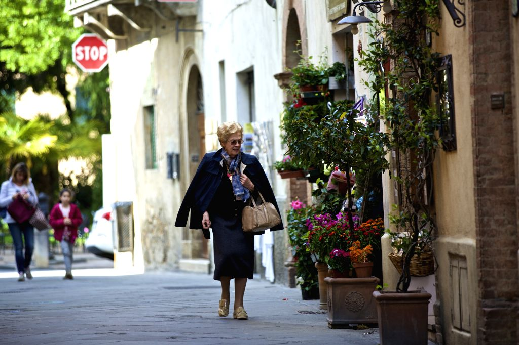 MONTALCINO, May 9, 2017 - A woman walks past Montalcino, Italy, on May 6, 2017. Montalcino is a medieval hill town in Tuscany of Italy. It is famous for the surrounding picturesque landscape depicted ...