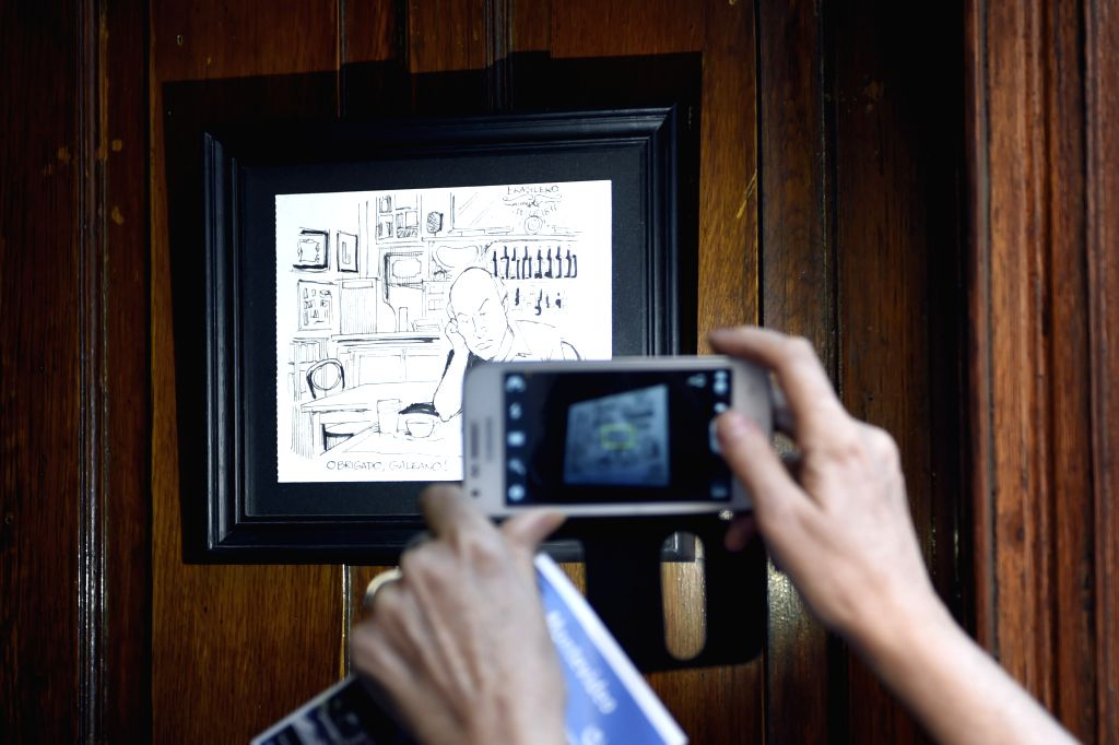 "A tourist takes a picture of a cartoon of the Uruguayan writer, Eduardo Galeano, in the ""Cafe Brasilero"", which he used to visit, in the Ciudad Vieja, ..."