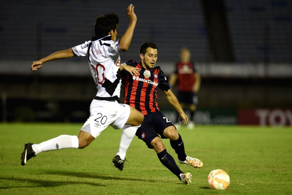 Danubio's Hamilton Pereira (L) of Uruguay vies for the ball with San Lorenzo's Sebastian Blanco of Argentina during the match of Libertadores Cup, at Centenario ...