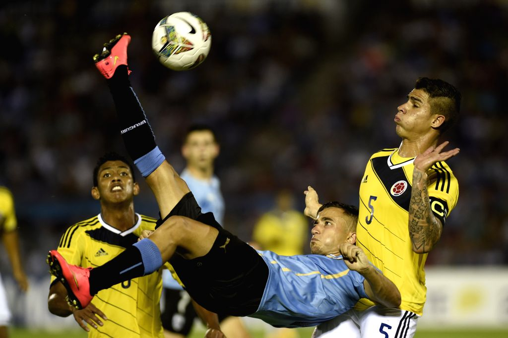Uruguay's Franco Acosta (C) vies for the ball with Colombia's Juan Quintero (R) during their final phase match of the South American U-20 tournament at the ...