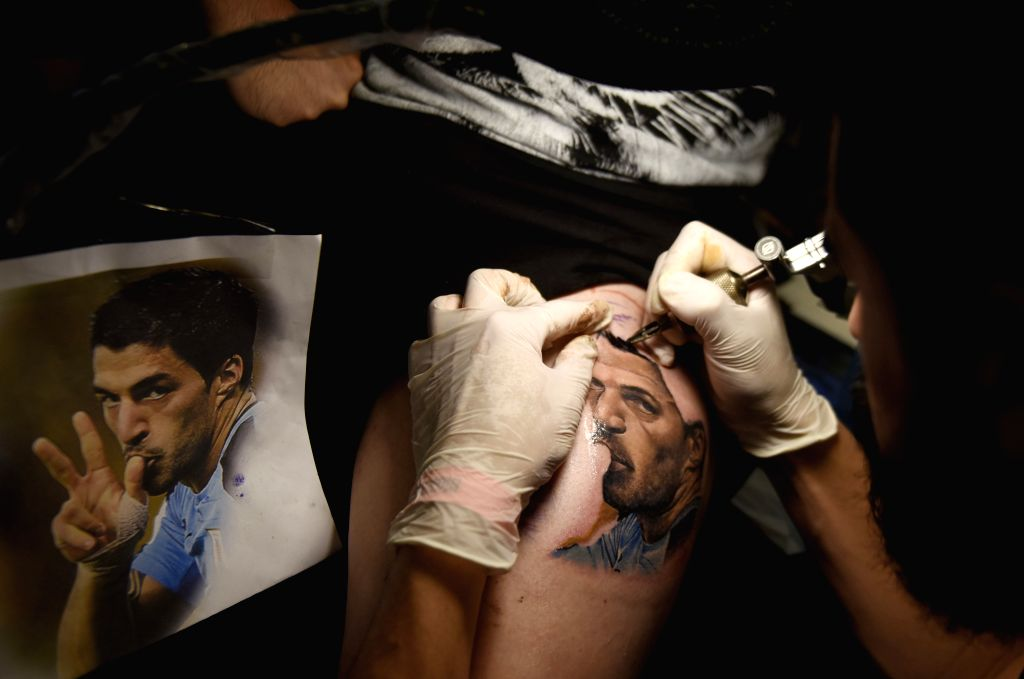 """MONTEVIDEO, Oct. 3, 2016 - An artist works on a tattoo on a client's leg during """"Tattoo Art 2016"""" in Montevideo, capital of Uruguay, on Oct. 2, 2016. A number of tattoo artists of South ..."""