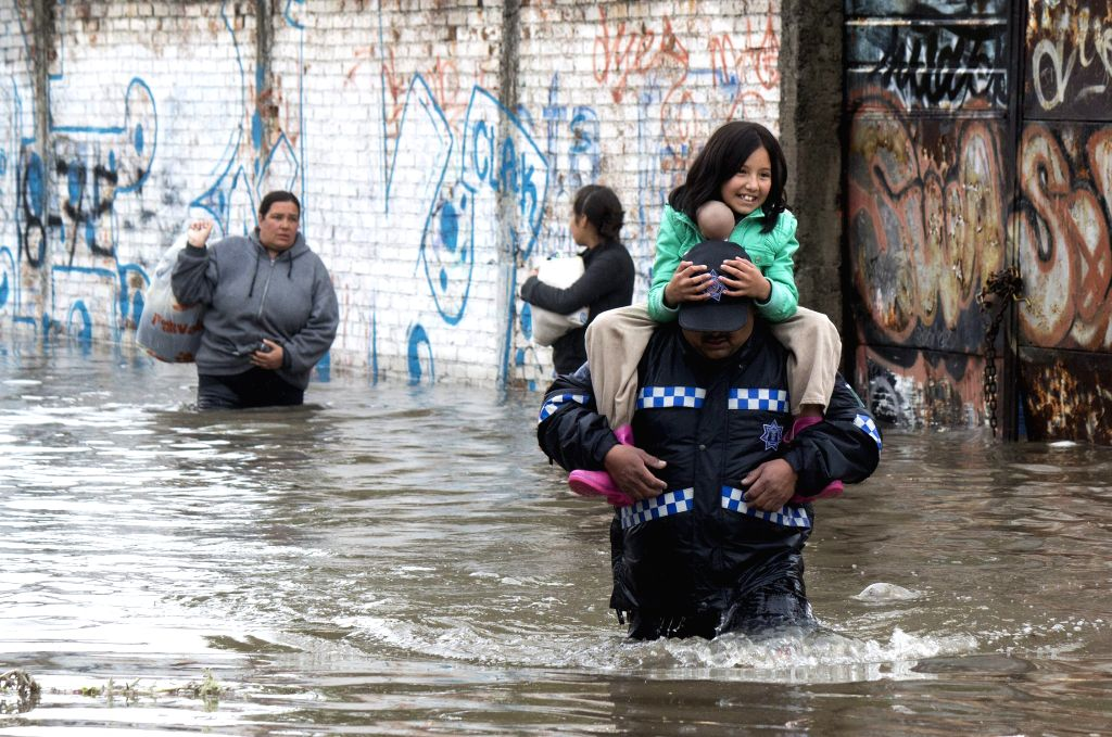 A policeman carries a girl on his shoulders, after a flood, in Morelia, Michoacan state, Mexico, on March 15, 2015. According to local press, the constant rains in ...