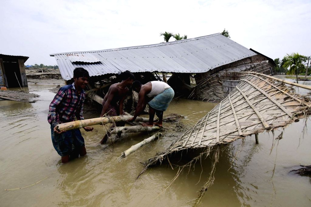 Morigaon: Flood-affected people attempt to rebuild their damaged hut at flood affected Laharighat Village in Morigaon district of Assam, on 21 July 2019. (Photo: IANS)
