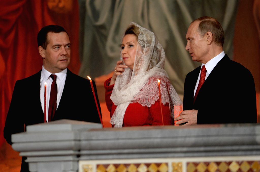 Russian Prime Minister Dmitry Medvedev, his wife Svetlana and Russian President Vladimir Putin (L to R) attend an Orthodox Easter service in Christ Savior Cathedral ... - Dmitry Medvedev