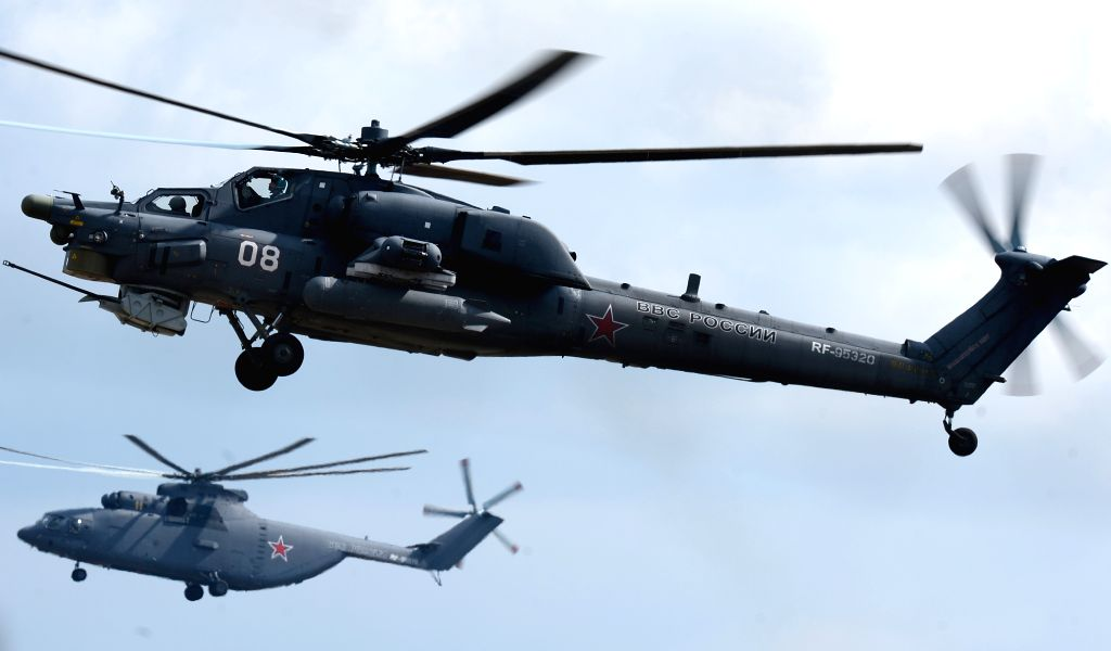 MOSCOW, April 20, 2016 - Russian anti-armor attack helicopter Mil Mi-28 (front) and Russian heavy transport helicopter Mil Mi-26 fly during the rehearsal of the aviation part of Victory Day parade in ...