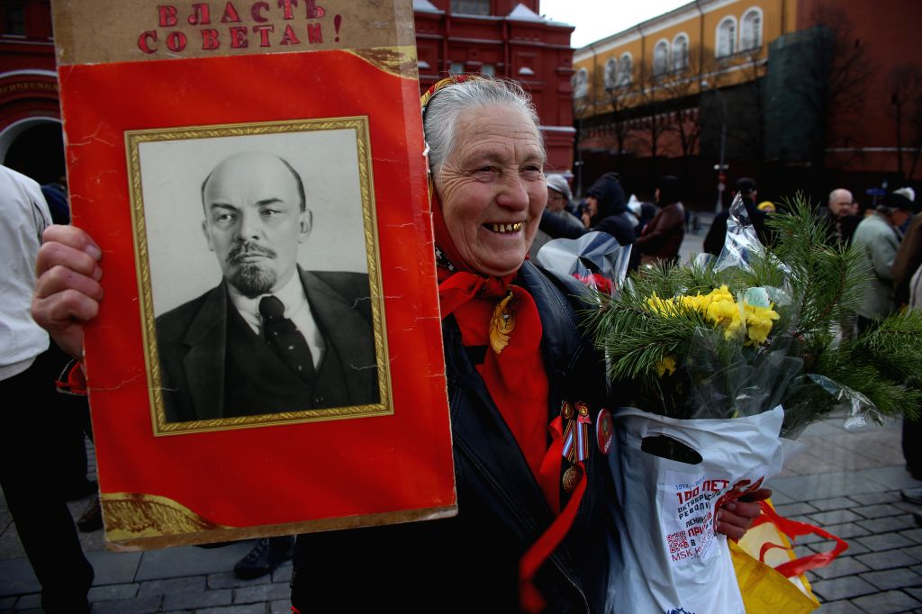 MOSCOW, April 22, 2016 - An elder woman holds flowers and a portrait of Vladimir Lenin during a laying flower ceremony at Lenin's mausoleum in Moscow, Russia, on April 22, 2016. People participated ...