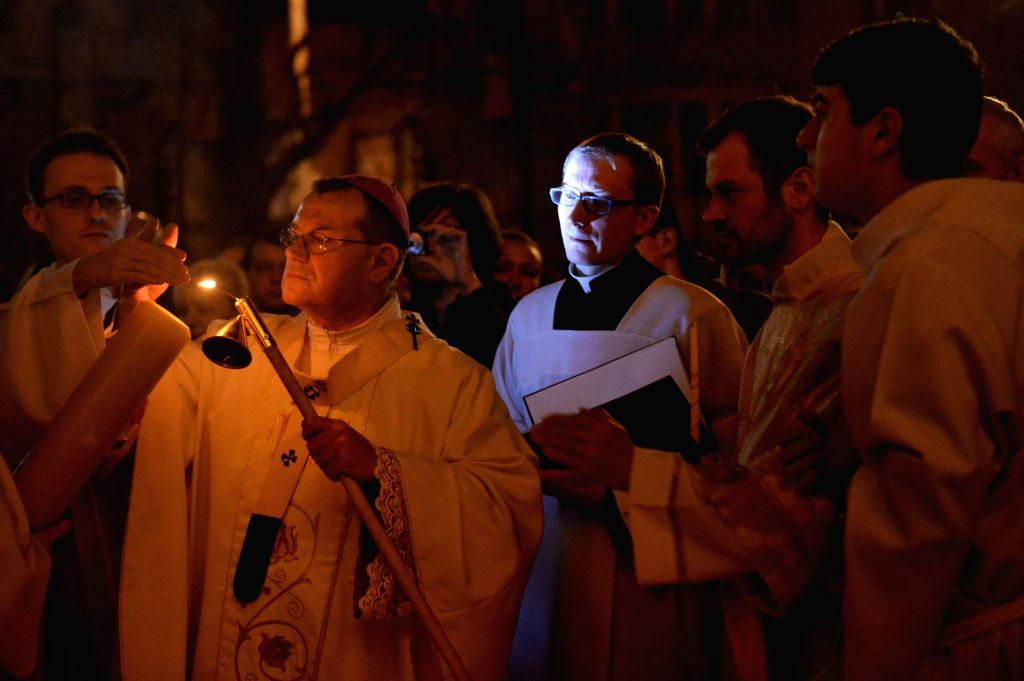 Archbishop Paolo Pezzi (2nd L) lights the Easter fire on the Pashal candle during the Easter service at the Cathedral of the Immaculate Conception in Moscow, Russia, ...