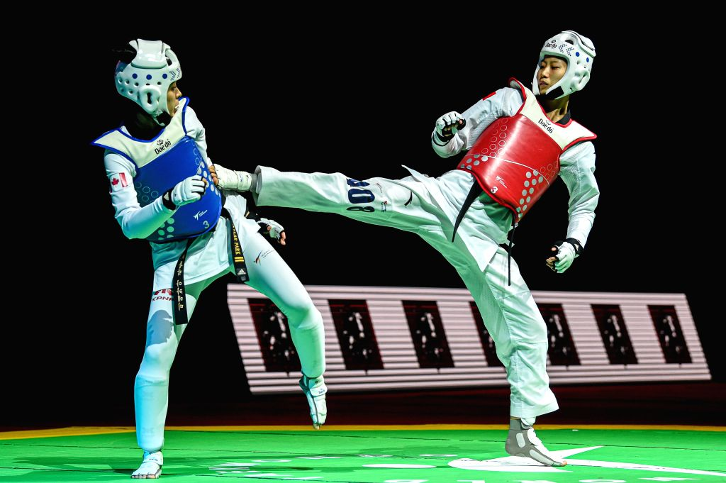 MOSCOW, Dec. 7, 2019 - Luo Zongshi (R) of China competes with Skylar Park of Canada during the women's -57kg semifinal at the 2019 World Taekwondo Grand Prix Final in Moscow, Russia, on Dec. 6, 2019.