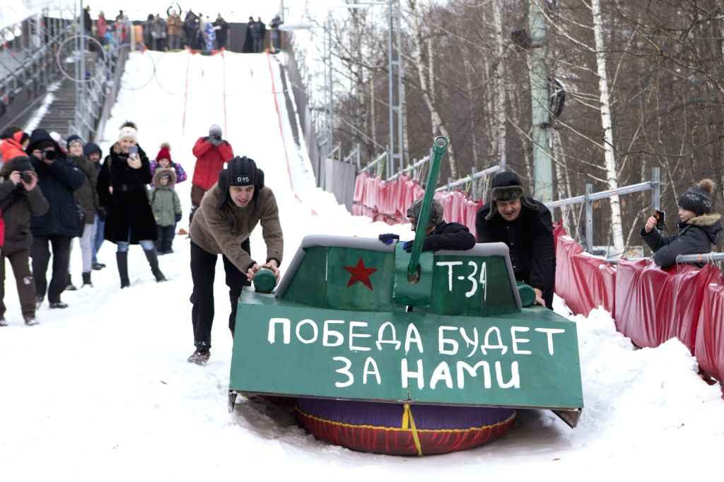 "MOSCOW, Feb. 23, 2019 - People push a sled decorated as a tank with the painted slogan ""Victory will be ours"" during a competition of handmade sleds in Moscow, Russia, on Feb. 23, 2019."