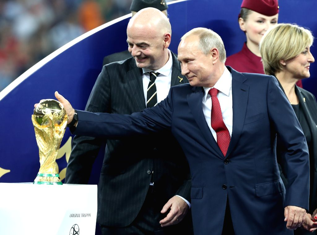 MOSCOW, July 15, 2018 - Russian President Vladimir Putin (R front) touches the World Cup trophy at the awarding ceremony after the 2018 FIFA World Cup final match between France and Croatia in ...