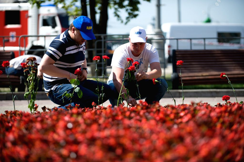Two men lay flowers near Park Pobedy station on July 16, 2014, in Moscow, Russia. Residents in Moscow laid flowers and lighted candles at the metro station to convey
