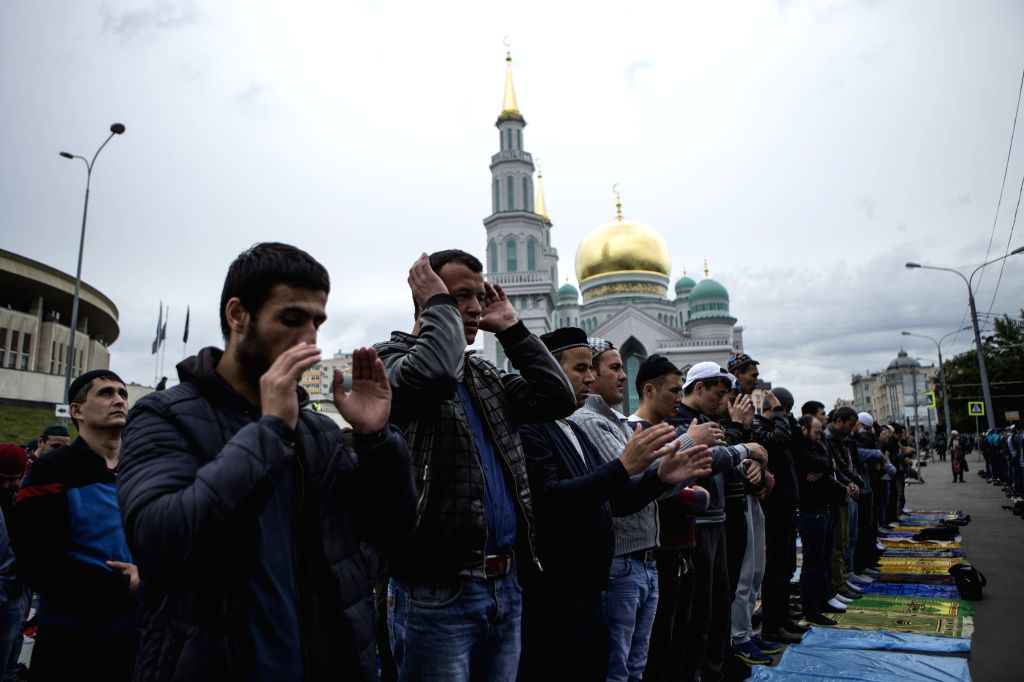 MOSCOW, June 25, 2017 - Muslim men perform Eid al-Fitr prayers that marks the end of the holy fasting month of Ramadan in front of central mosque in Moscow, Russia, on June 25, 2017.  Thousands of ...
