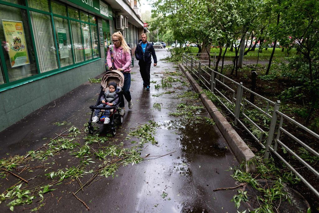 MOSCOW, May 29, 2017 - People walk past fallen branches of trees after a storm in Moscow, Russia, on May 29, 2017. A sudden storm killed at least 11 people in Moscow Monday afternoon and forced 50 ...