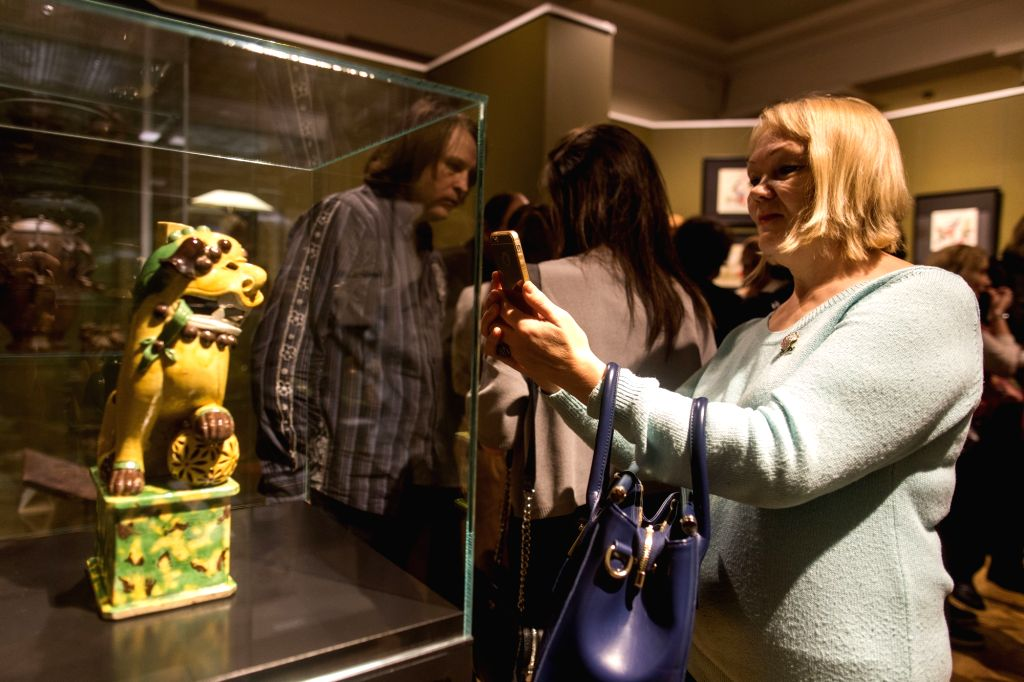 """MOSCOW, Oct. 13 A woman takes a photo at the exhibition """"Secrets of the Celestial Empire"""" in Moscow, Russia, on Oct. 12, 2017. The exhibition, held from October 12 to November ..."""