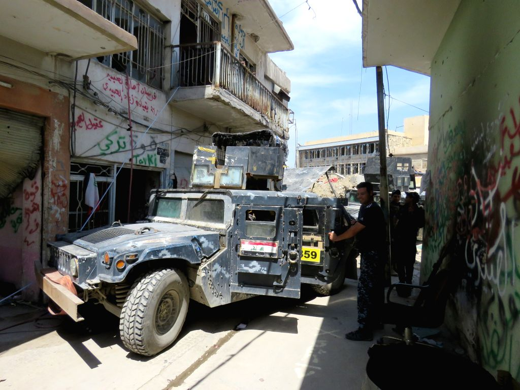 MOSUL (IRAQ), May 7, 2017 A member of Iraqi Federal Police stands by a military vehicle in south of the Old City in western Mosul, Iraq, on May 7, 2017. A group of Iraqi Federal Police ...