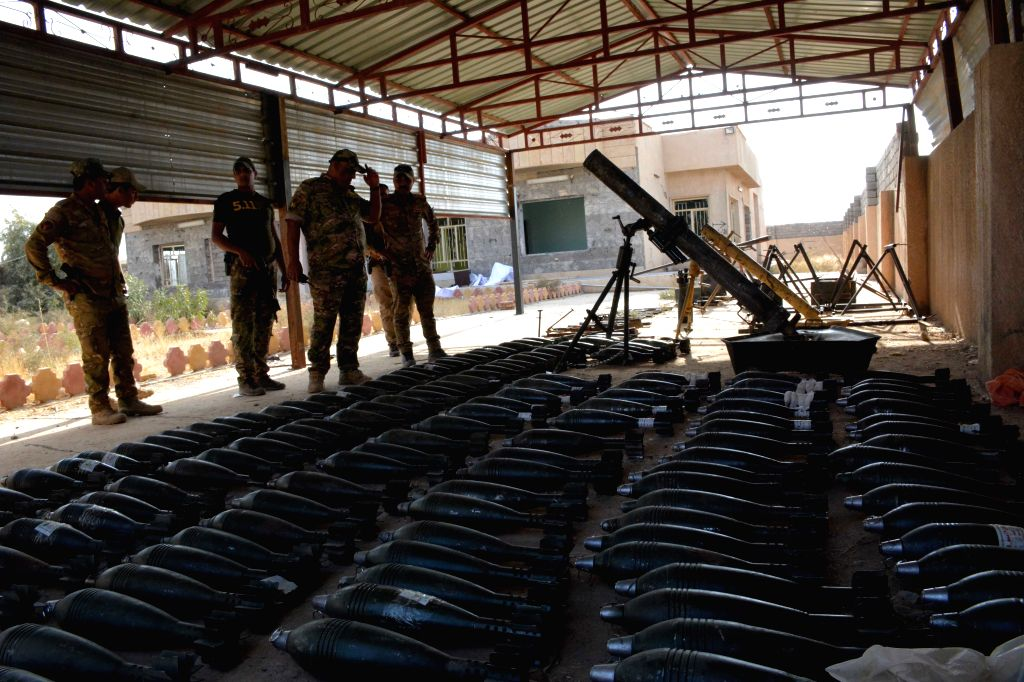 MOSUL, Oct. 30, 2016 - Iraqi officers look at weapons seized from the Islamic State(IS) militants in Shoura town, 30 km south of Mosul in northern Iraq, on Oct. 30, 2016. The Iraqi security forces on ...