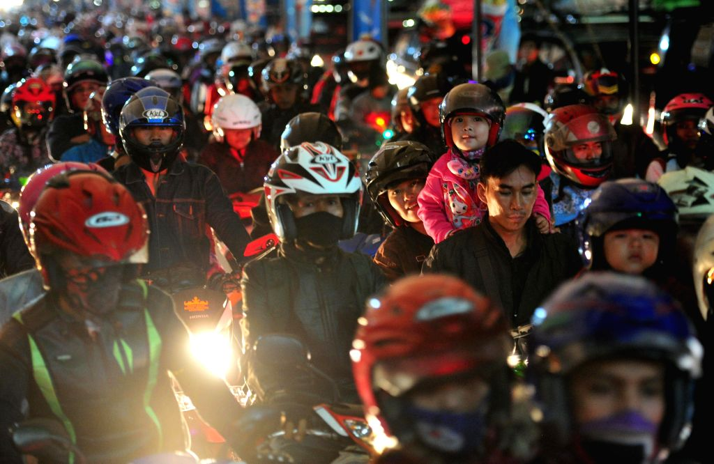 Motorbike riders queue to board a ferry ship at Merak port in Banten, Indonesia, on July 15, 2015. Indonesia's traffic reaches its peak as millions of people travel ...