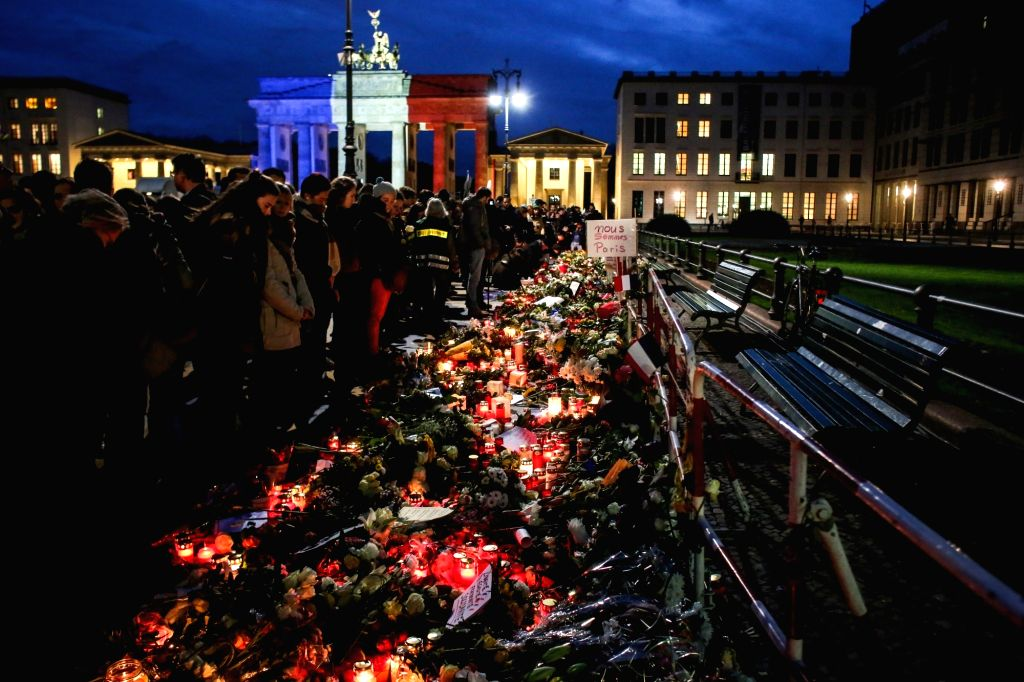 Mourners attend a gathering in memorial of the victims killed in the Friday's attacks as the Brandenburg Gate is illuminated in the French national colors in Paris ...
