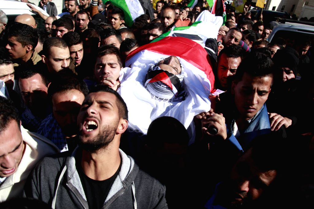 Mourners carry the body of 22-year-old Hasan Al-Bau, who died after being hit in the heart by live ammunition during clashes with the Israeli army the previous day, ...