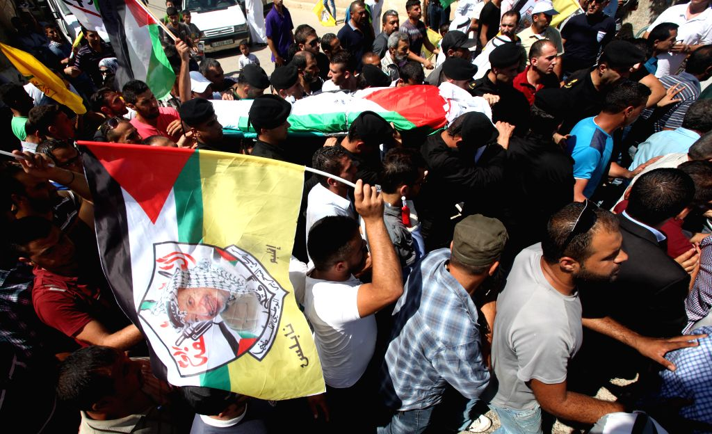 Mourners carry the body of the Palestinian Sa'ed Dawabsha who died after being injured when his family house was set on fire by Jewish settlers on July 31, during his ...